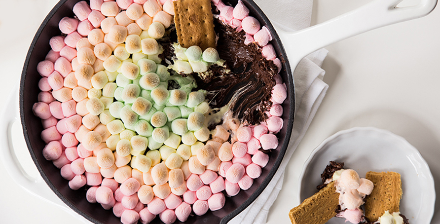 skillet with warm chocolate chips and colorful marshmallows to dip graham crackers in