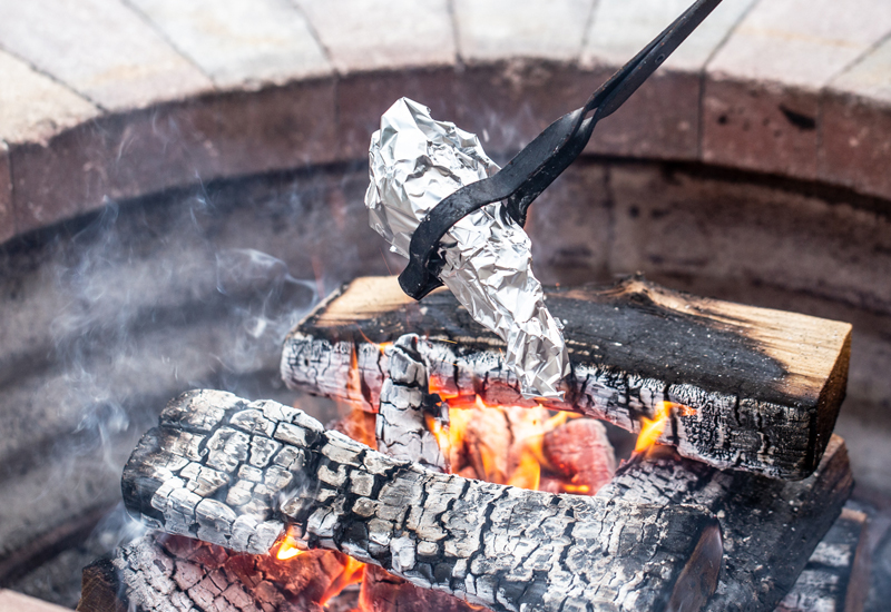 using tongs to heat a s'mores cone over campfire